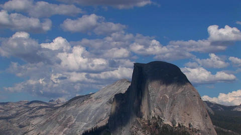 A time lapse of white clouds over a blue sky and rocky mountain range in Yosemite National Park, Cal Footage