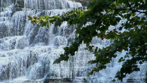 Water cascades down a multi layered rock hillside in Ithaca Falls, New York Footage