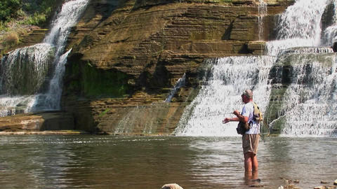 A fisherman stands at the bottom of a wide waterfall... Stock Video Footage