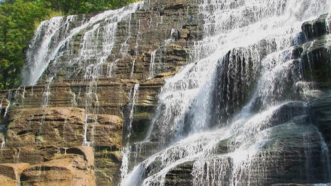 A wide waterfall flows over rock ledges in Ithaca Falls,... Stock Video Footage