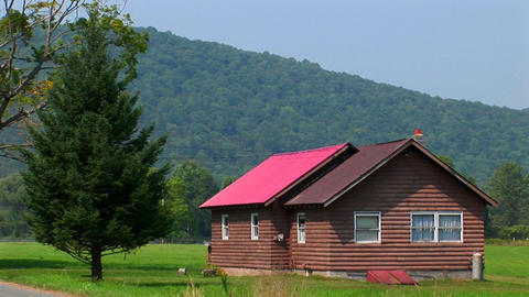 A cabin in the middle of a green field near the Allegheny Mountains in West Virginia, Pennsylvania Footage