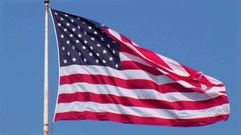 An American flag flies in the wind at day Footage