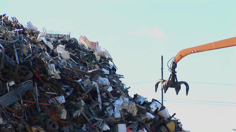 An arm grapple sorts through a high pile of waste Stock Video Footage