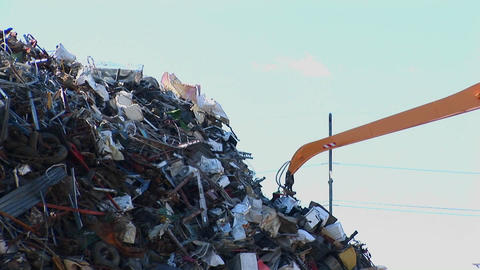 An arm grapple sorts through a high pile of waste Footage