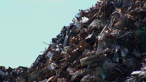 Vehicles drive pass a high pile of waste Stock Video Footage