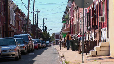 A woman walks down a sidewalk near vehicles parked along brick buildings in Philadelphia, Pennsylvan Footage
