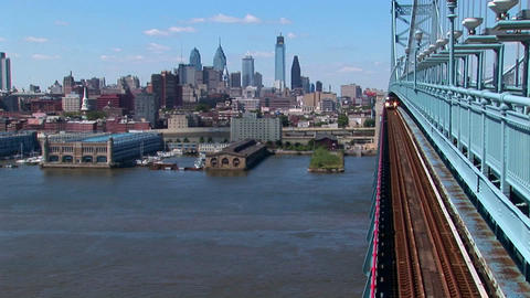A rapid transit train drives across Ben Franklin Bridge... Stock Video Footage