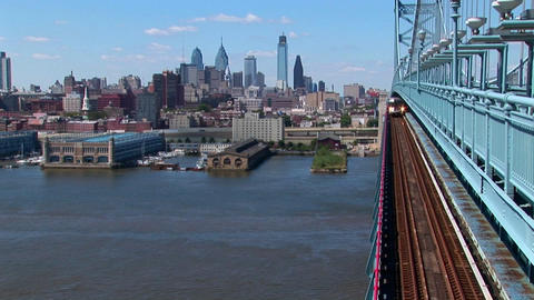 A rapid transit train drives across Ben Franklin Bridge... Stock Video Footage