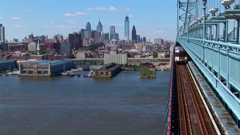 A rapid transit train drives across Ben Franklin Bridge away from Philadelphia, Pennsylvania Footage