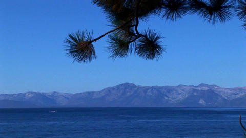 Clear, blue water in Lake Tahoe stretches out toward the base of the Sierra Nevada mountains Footage