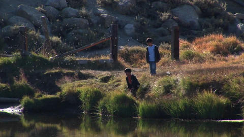 young boys explore a lake near the Sierra Nevada Mountains Stock Video Footage