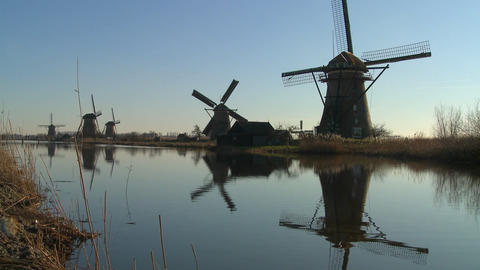 Windmills line a canal in the Netherlands Footage
