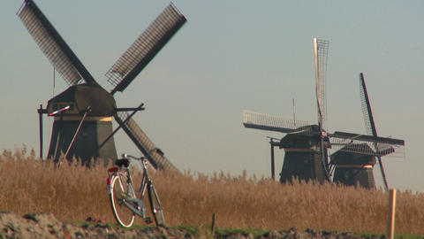 A bicycle is parked along a path in Holland with windmills in the background Footage