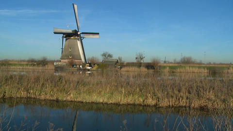 A windmill rises above a canal and grass in Holland Stock Video Footage