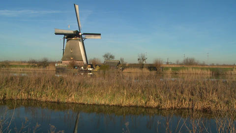 A windmill rises above a canal and grass in Holland Footage