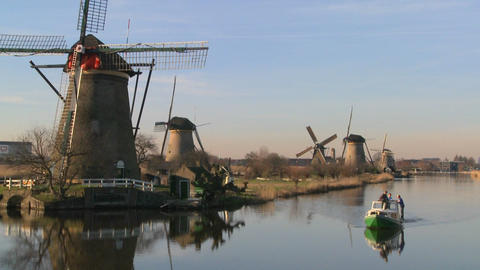 A boat moves along a canal in Holland with windmills nearby Footage