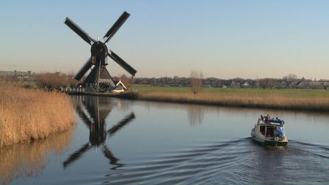 A boat moves along a canal in Holland with windmills nearby Stock Video Footage