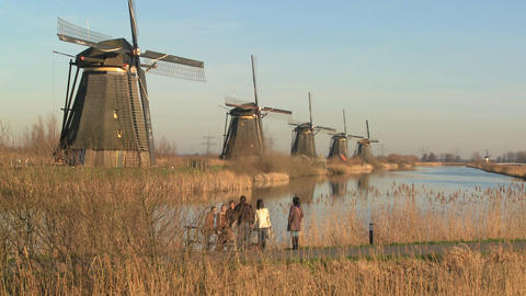 Many windmills line up in a perfect row along a canal in... Stock Video Footage
