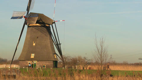 A woman pushes a baby carriage along a path near a windmill in Holland Footage