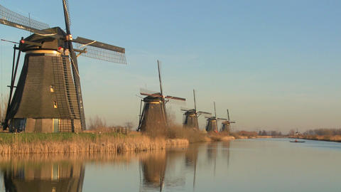 Windmills line up perfectly along a canal as a small boat... Stock Video Footage