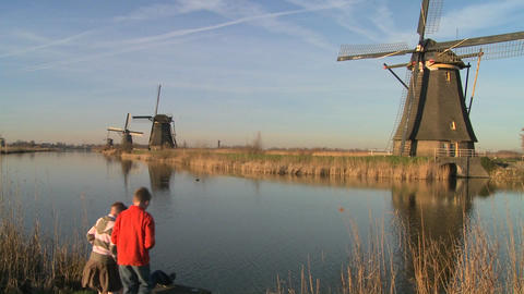 children play beside a canal and windmills in Holland Stock Video Footage