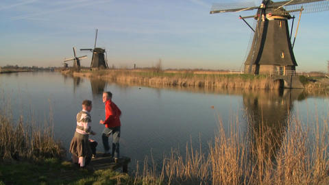 children play beside a canal and windmills in Holland Footage