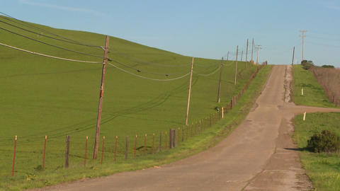 A country road moves along beside green fields Stock Video Footage
