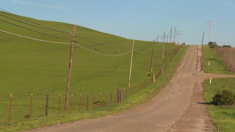 A country road moves along beside green fields Footage