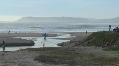 A surfer walks across an estuary along the Central California coast Footage