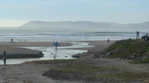 A surfer walks across an estuary along the Central California coast Footage