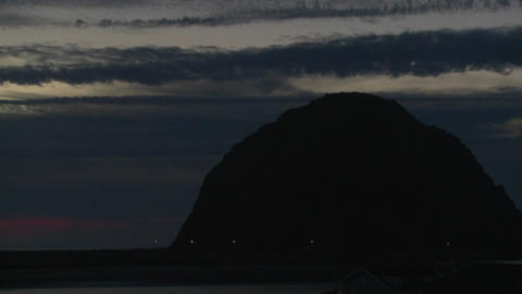 A time lapse shot over a dark round mountain at Morro Bay, California Footage