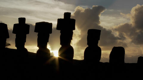 The sun peeks out from behind an Easter Island statue Stock Video Footage
