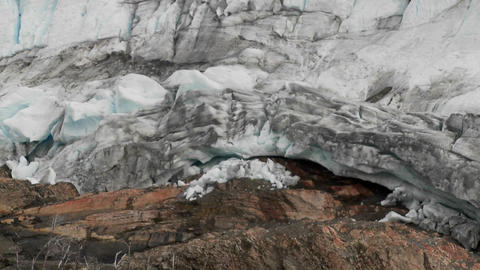 Pan across a glacier to where it meets the land Stock Video Footage