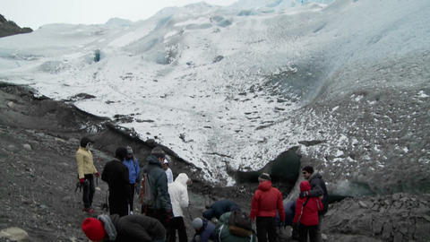 Hikers gather at the base of a glacier for a trek Footage