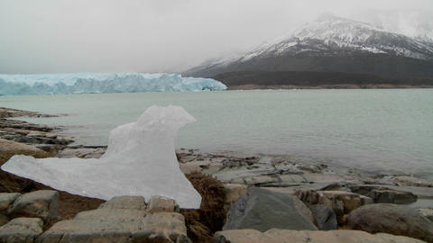 A melted piece of a glacier sits on dry land in this shot suggesting global warming Footage
