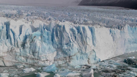 Pan across a vast glacier where it meets the sea Stock Video Footage
