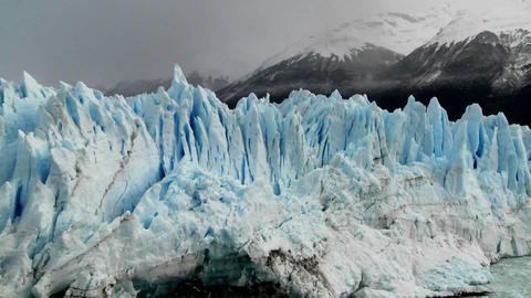 The spiked tops of a glacier stand against rugged mountains Stock Video Footage