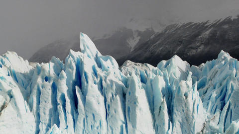 The spiked tops of a glacier stand against rugged mountains Footage