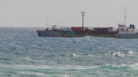 Waves roll into a rocky shore with a freighter ship in... Stock Video Footage