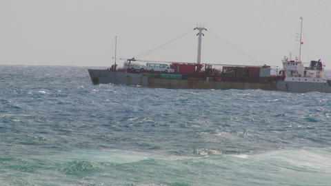 Waves roll into a rocky shore with a freighter ship in the background Footage