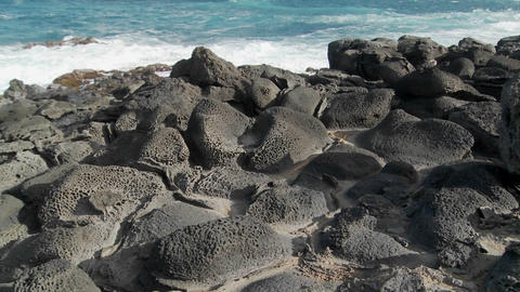 Pan across a rocky volcanic shoreline on a tropical island Stock Video Footage