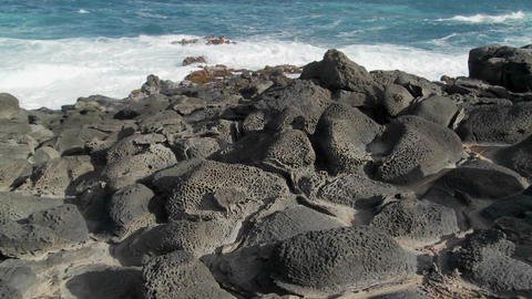 Pan across a rocky volcanic shoreline on a tropical island Footage