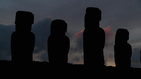 A long line of statues is silhouetted on Easter Island in this dusk shot Footage