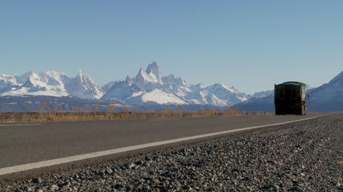 A truck passes on a remote highway in Southern Argentina with the Fitzroy mountain range in backgrou Footage