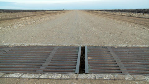 A steel metal grate cattle guard on a lonely road Stock Video Footage