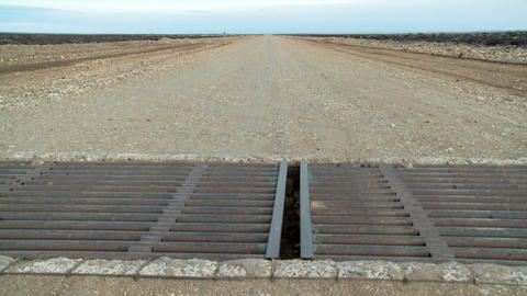 A steel metal grate cattle guard on a lonely road Footage