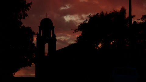 An old California style mission bell tower against a sunset sky Footage