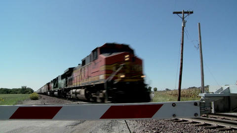 A freight train speeds past a gated railroad crossing Stock Video Footage
