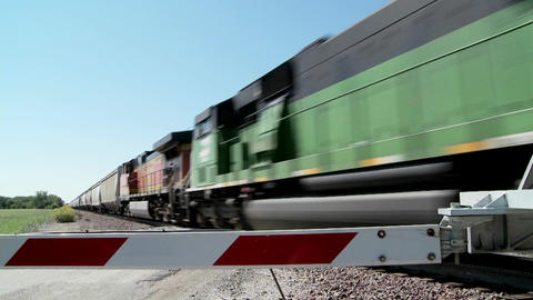 A freight train speeds past a gated railroad crossing Footage
