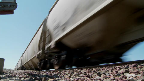 Low angle of a train passing with roadbed in foreground Stock Video Footage